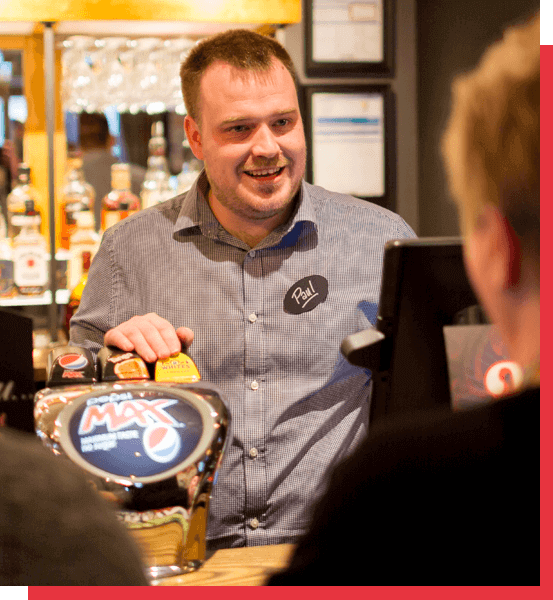 Happy barman serving a drink at a Marstons Pub
