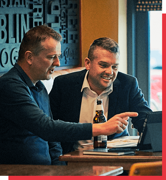 two pub managers looking at a laptop